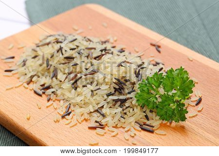 pile of wild rice on wooden cutting board - close up