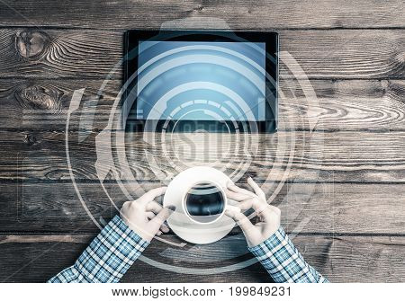 Top view of woman in checked shirt sitting at wooden table with tablet pc