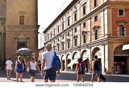 BOLOGNA, ITALY, 02 AUGUST 2017.  People walking in the historic center of bologna on a hot summer day in summer clothes, defending themselves from the sun with umbrella, 02 august 2017.