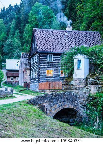Old traditional timbered cottage with romantic with stone bridge at evening time. Czech rural architecture.