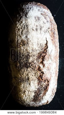 Beautiful Organic Whole Wheat Sourdough Bread on a dark table