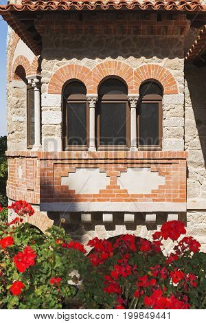 Beautiful triple arch window in a stone house decorated with orange bricks