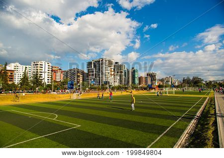 Quito, Pichincha Ecuador - August 10 2017: Unidentified people playing soccer inside of the Carolina park north part of the city of Quito, in a sunny day, blue sky.
