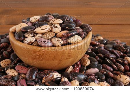 Raw purple, pink, beige with brown speckled kidney beans on wooden bowl at brown wooden table. Closeup