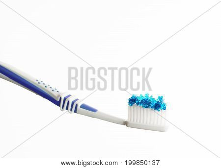 isolated toothbrush with blue colored sugar on it in front of white background