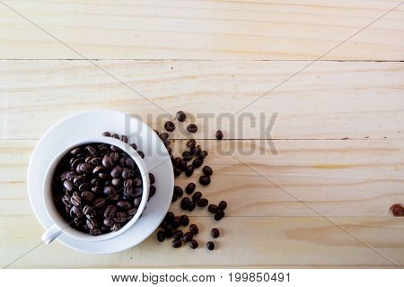 White cup with coffee grains on a wooden table-top. The scattered grains of fried coffee. The top view on a table.