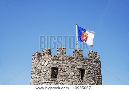 A tower of west wall of the Moorish Castle with a Portuguese flag in Sintra Portugal