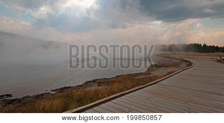 Boardwalk curving around Hot Lake hot spring in the Lower Geyser Basin in Yellowstone National Park in Wyoming United States