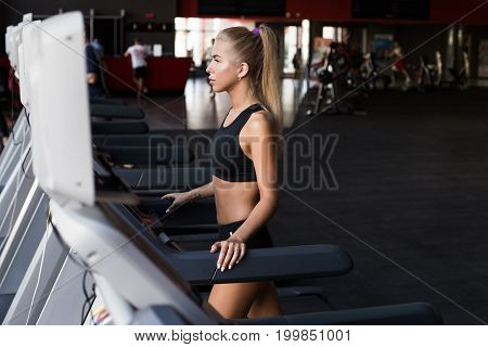 Beautiful sport trainer run on a treadmill. Young blond slim fitness girl standing in modern gym preparing for workout