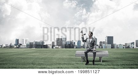 Young businessman sitting on bench and screaming emotionally in megaphone