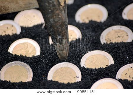 Euro coins in black sand close up photo with hammer