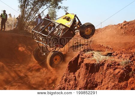 Yellow Car Ramping Out Of Steep Dugout, Front Wheels Suspended, Kicking Up Sand And Dust.