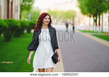 Portrait of an attractive businesswoman walking through a tree lined street in the financial district of a classic city.