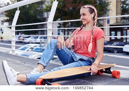 Wide shot of wonderful blonde woman relaxing while sitting under handrail with skateboard