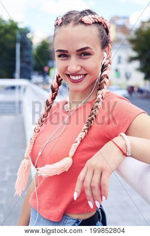 Vertical of attractive blonde leaning on handrail and listening to music