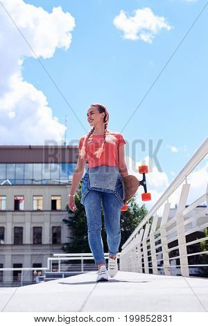 Vertical of gorgeous blonde walking with skateboard in hands with copy space