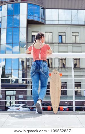 Rear view of slim woman having break after riding skateboard with copy space