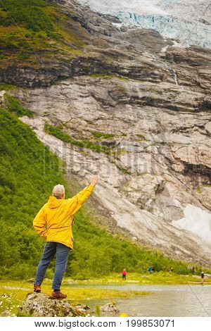Adventure hiking man admiring Boyabreen Glacier in Fjaerland area Sogndal Municipality in Sogn og Fjordane county Norway. Tourist visiting norwegian nature landscape.