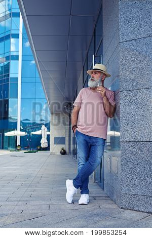 Full-length image of handsome bearded male with electro cigarette holding hand in pocket and looking at something aside, warm day mid shot
