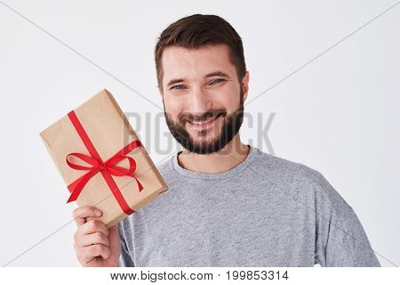 Close-up shot of elated bearded man in grey t-shirt holding a present box. Man wearing casual clothes posing at the camera in the studio, copy space