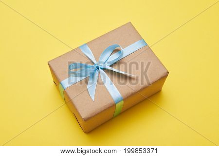 Flat lay of beautiful present with box decorated with blue ribbon on yellow background