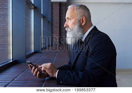 Mid shot of grim male looking out window while working in phone and leaning on sill