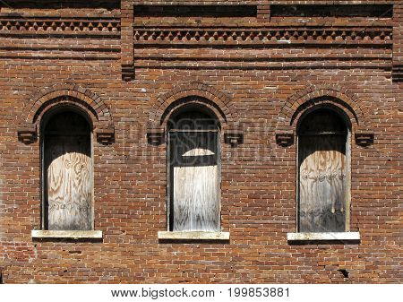 Boarded up windows of an old brick building in Belton, Texas
