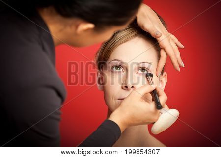 Detail shot of a stylist making up a young woman