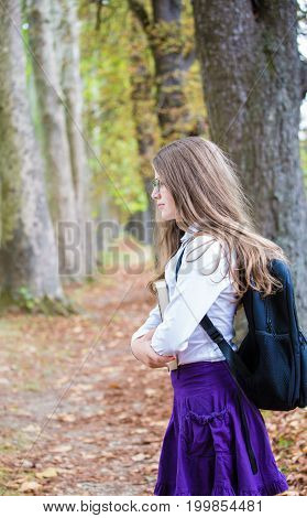 Pretty Little Long Hair Blonde Schoolgirl With Backpack Posing In The Alley Park Holding Books Back