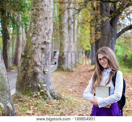 Pretty Beautiful Blonde Child Schoolgirl Back To School Standing, Posing And Smiling In Tree Alley I