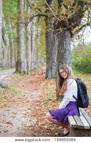 Pretty Beautiful Blonde Child Schoolgirl Smiling Back To School Sitting On Bench In Tree Alley In Na