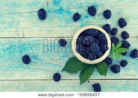 Close Up Of Ripe Blackberries In A White Ceramic Bowl Over Rustic Wooden Background. Top View