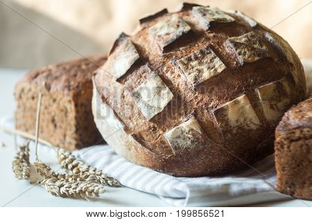 Tasty rustic bread and ears of wheat on table