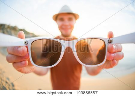 Handsome young man puts on camera sunglasses on the beach. Travel, fun, summer and vacation concept.