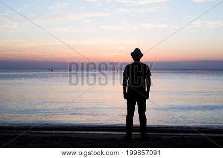 Man silhouette stand alone on stony beach and watching romantic colorful sunrise