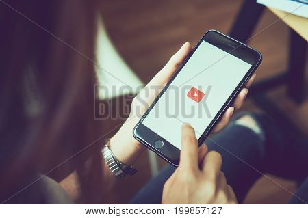 Bangkok, Thailand - August 16, 2017 : woman hands holding apple iPhone 6s on screen displays the Youtube app on the touch screen. YouTube is the popular online video-sharing website.