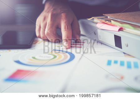 businessman hand working laptop on wooden desk in office in morning light. The concept of modern work with advanced technology. vintage effect