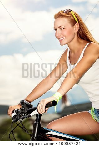 Beautiful happy woman riding the bicycle in countryside, pretty female enjoying time spending on open air, healthy lifestyle, active summer vacation
