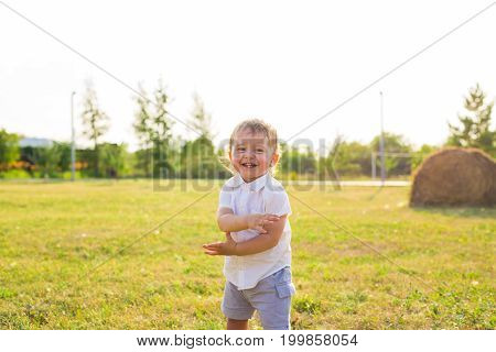 smiling boy in the field at sunny summer morning. boy in white shirt. The family travels, child happily ran around the field.