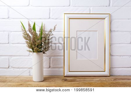 Gold Decorated Frame Mockup With  Grass And Green Leaves In Cylinder Vase