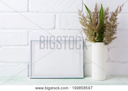 White Landscape Frame Mockup With  Grass And Green Leaves In Cylinder Vase