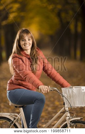 Smiling young woman on bike in Autumn park