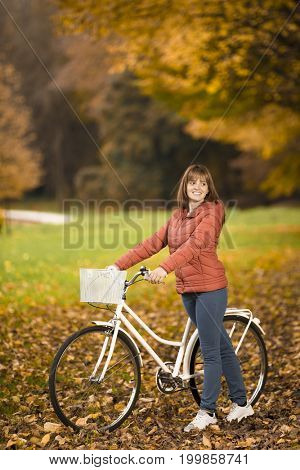 Woman standing with bike in Autumn park