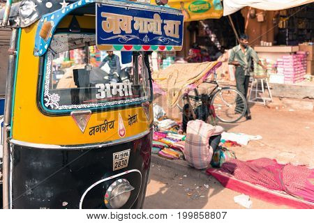 JODHPUR RAJASTHAN INDIA - MARCH 04 2016: Horizontal picture of the front of tuk tuk and local people at the Sadar Market in Jodhpur the blue city of Rajasthan in India.