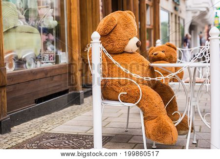 Teddy Bear sitting on a chair in street cafe.