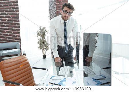 serious businessman standing near the desktop