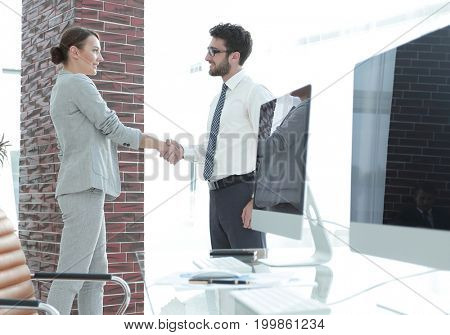 handshake of business partners on background of blank screens
