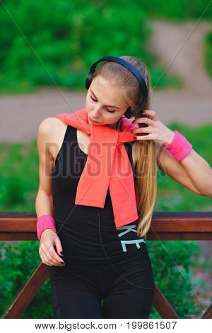 Cheerful young sportswoman listening to music from mobile phone and singing over yellow background