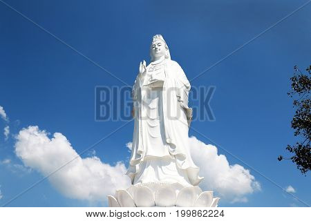 Majestic white Buddha statue on blue sky background. The Lady Buddha (the Bodhisattva of Mercy) at the Linh Ung Pagoda in Danang (Da Nang) Vietnam.