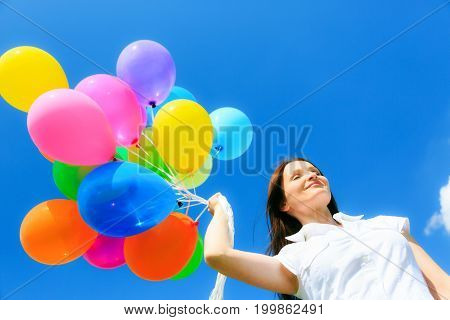 woman in fonr t of blue sky, holding colorful balloons